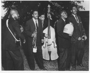 "Photo of Henry Miles Jug Band, circa 1960. From left, Chester Mason, guitar; Ken Tyler, trumpet; George Stewart, bass; Rudolph, jug; John ""Preacher"" Stephens, spoons."