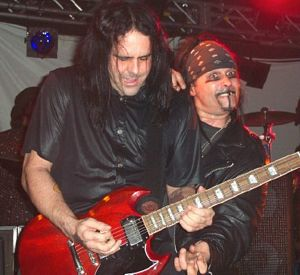 Photo of Ministry in action: On the left guitarist Mike Scaccia, and the goofy madman on the right is vocalist Al Jourgensen.