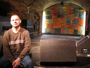 Photo of Kevin Gibson sitting on the stage at the Cavern Club